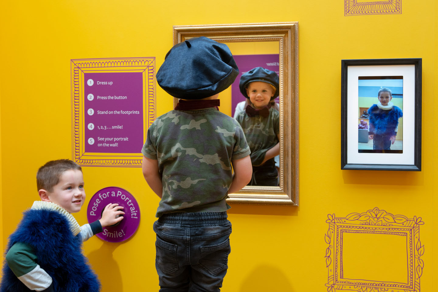 Two children dress up, one wearing a beret in front of a mirror