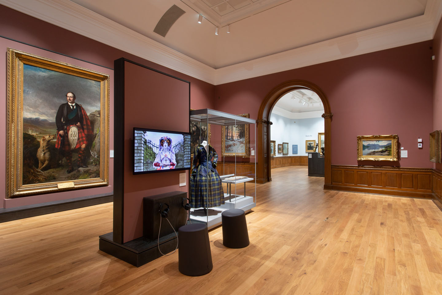 View through a gallery with paintings, TV screen and arch