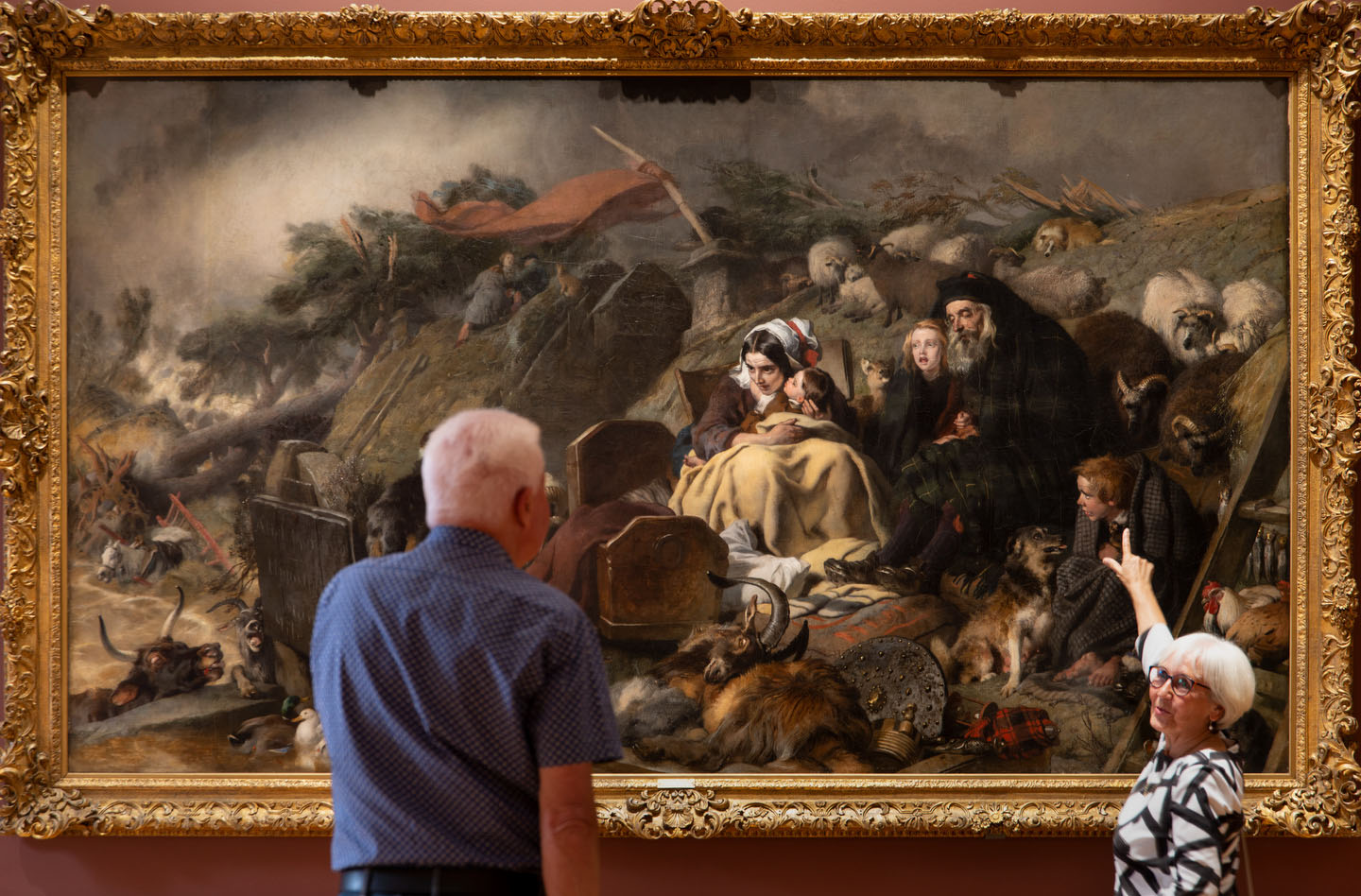 Two older visitors look at a huge painting of figures in an apocalyptic landscape