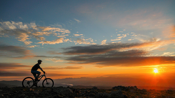Silhouette of a cyclist against a sunset