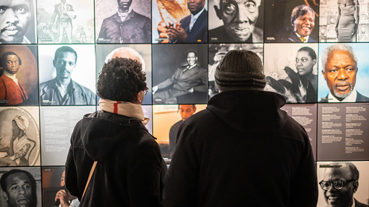 Two people looking at a display of images at the International Slavery Museum