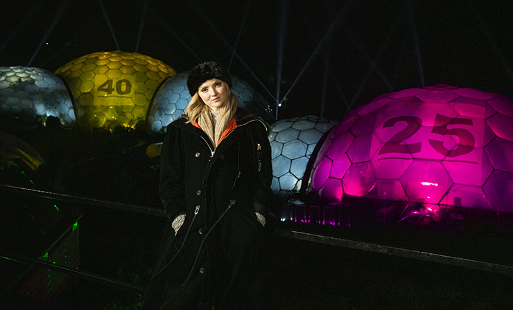 Lily Cole in front of the illuminated Eden Project Biomes