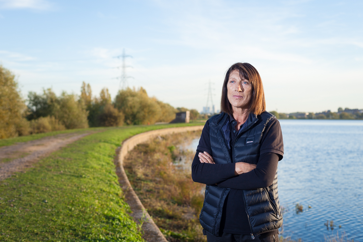 A woman stands in front of a reservoir